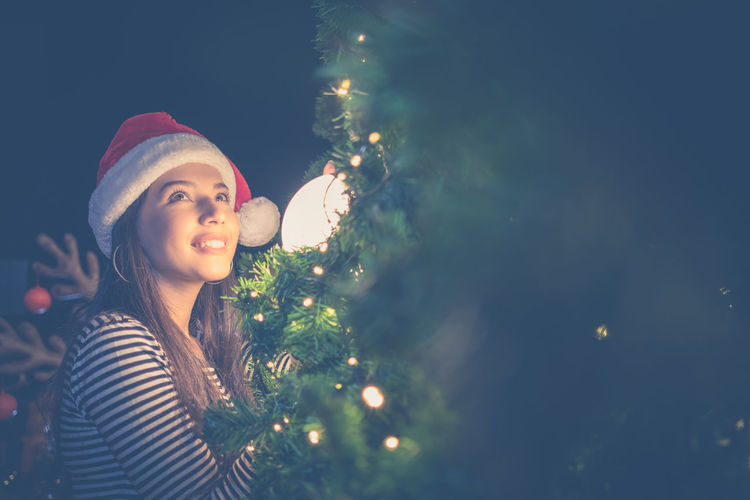 Smiling woman by illuminated christmas tree at night
