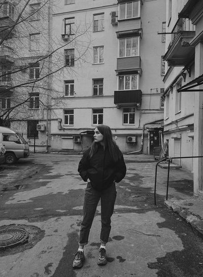 Rear view of man standing on street amidst buildings
