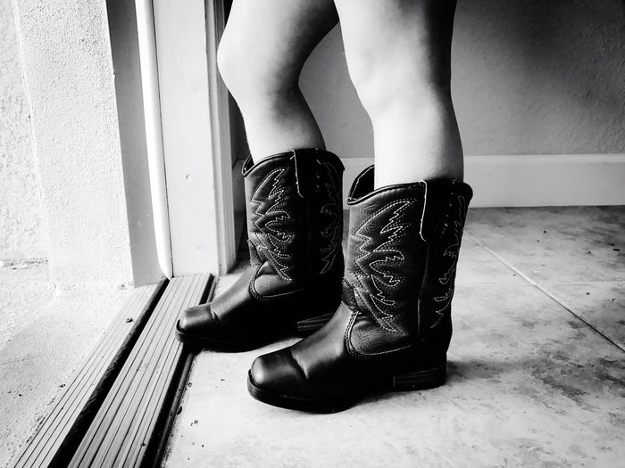 Low section of child wearing boots by doorway