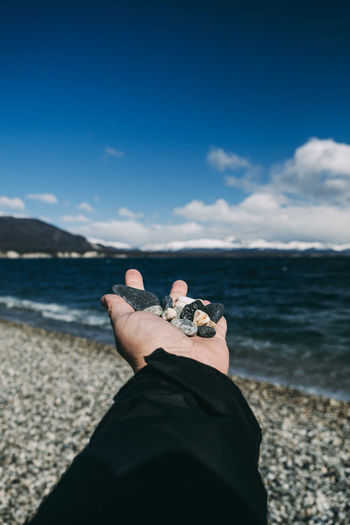Cropped hand of man holding pebble against sky