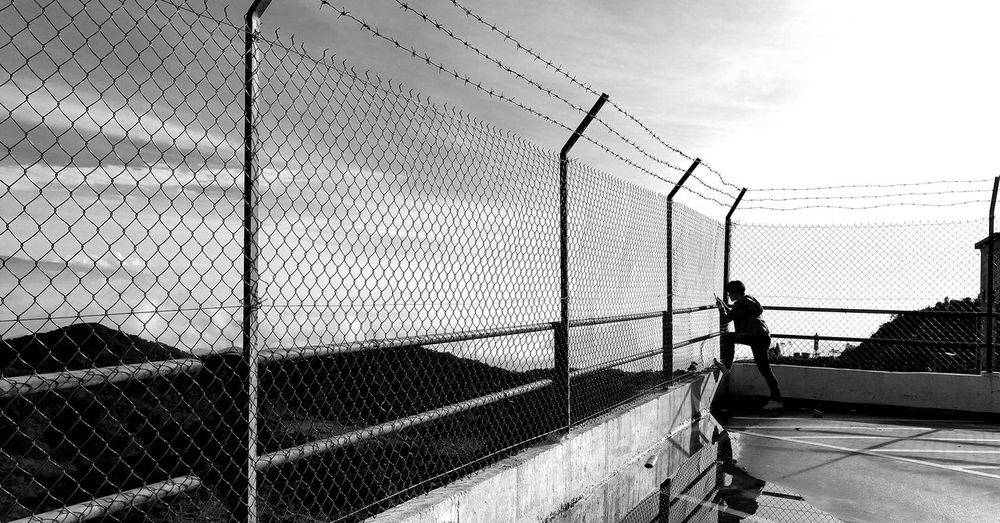 Side View Of Mid Adult Man Standing By Fence Against Sky