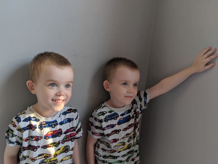Twin brother standing by wall