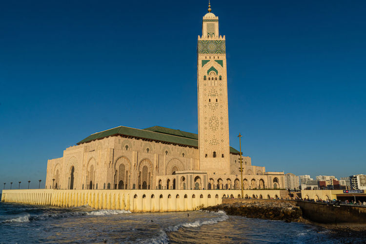 View of hassan ii mosque against blue sky in casablanca, morocco.