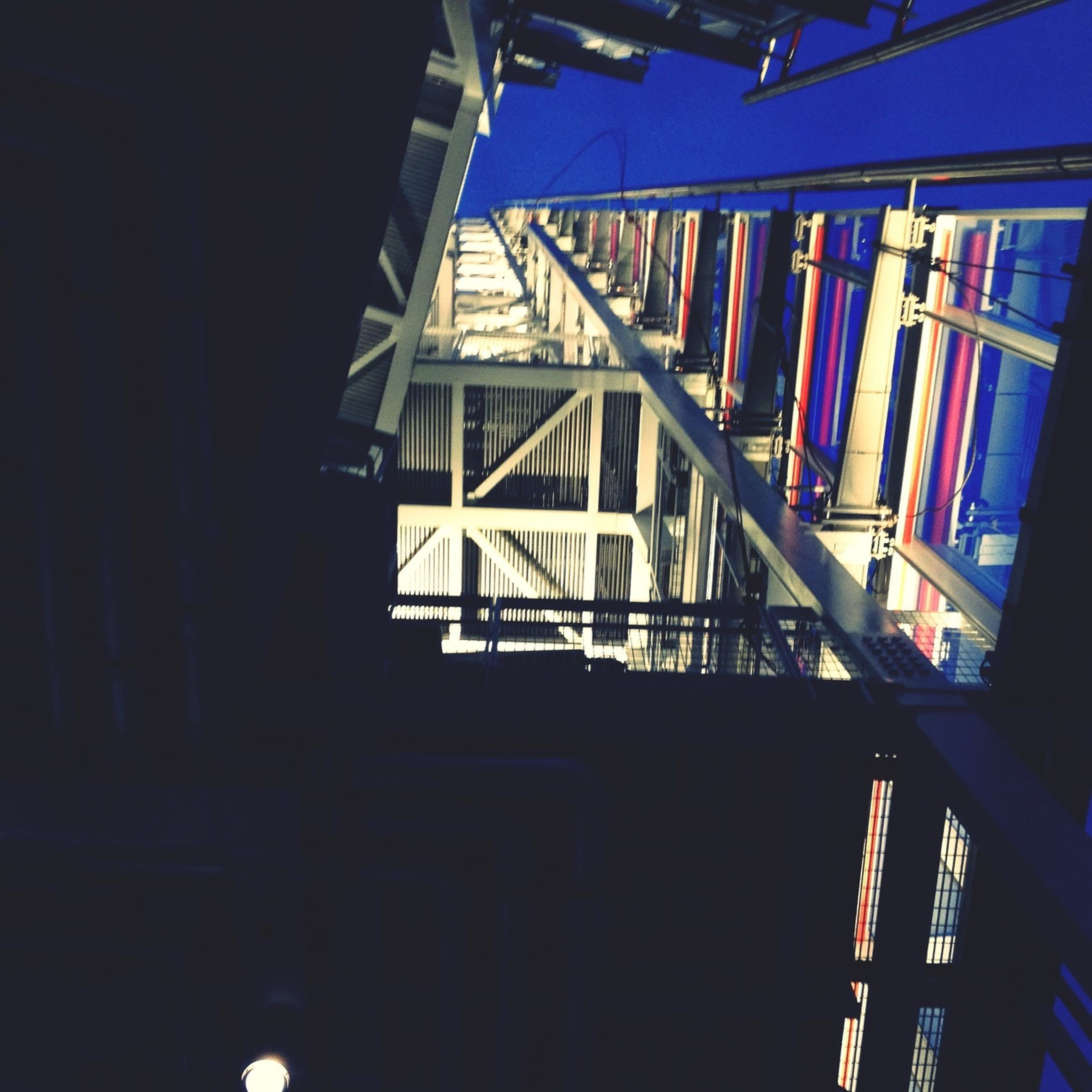 low angle view, architecture, built structure, building exterior, indoors, building, no people, in a row, window, balcony, sky, day, hanging, sunlight, blue, residential structure, house, multi colored, residential building, modern