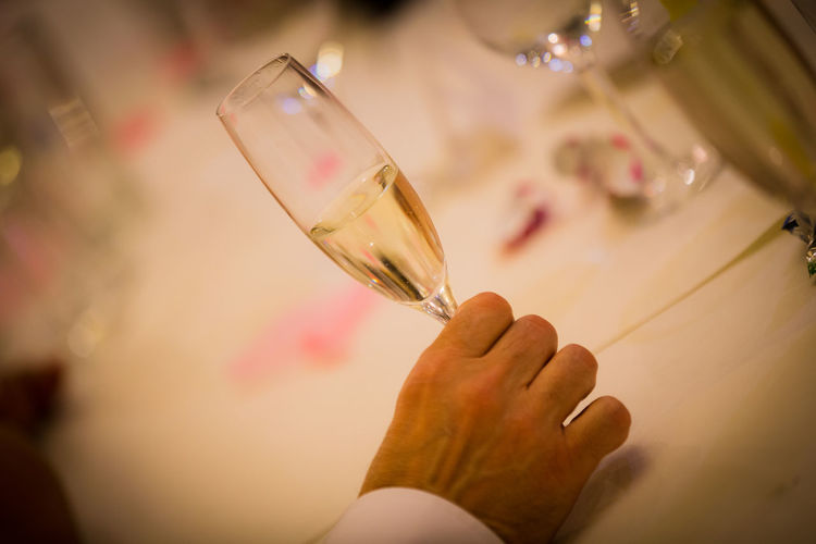 Cropped hand of man holding champagne flute at table
