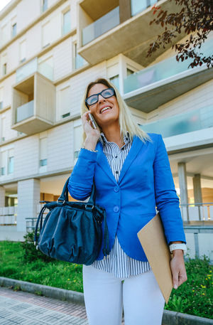 Happy businesswoman talking on the mobile in the street Business Happy Sunlight Woman Worker Working Business Finance And Industry Businesswoman Caucasian Dossier Executive  Flare Lifestyles Office Building Office Building Exterior One Person Phone Professional Real People Smart Phone Street Sun Talking Vertical Young Adult