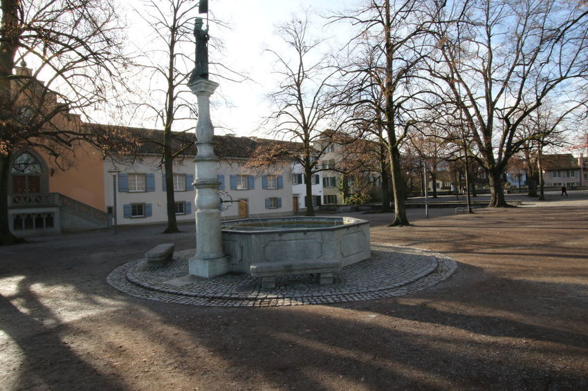 Hedwig Fountain - Lindenhof, Zurich. Hedwig Fountain, with a statue commemorating the 1291 defense of the town by the women of Zurich against Albert I of Germany. Once the site of a Roman fort, and later a palace of Charlemagne's grandson, Lindenhof is listed as a Swiss heritage site of national significance. http://pics.travelnotes.org/ Fountain Houses Shade Travel Travel Photography Trees View Zürich Architecture Bare Tree Building Exterior Built Structure City Clear Day Day Lindenhof Lindenhof Zürich Outdoors Shadow Sky Still Townhouses Travel Pics Trees And Sky Wide Angle