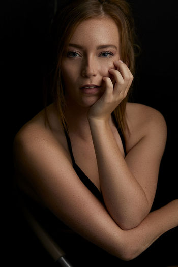 Portrait Of Beautiful Young Woman With Hand On Chin Against Black Background