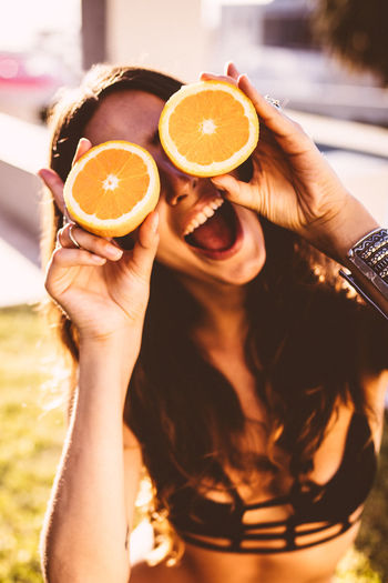 Cheerful Woman Covering Her Eyes With Sliced Oranges