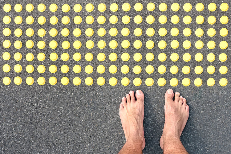 Barefoot on asphalt road at tactile bumps paving - Life concept of human feeling with bare feet of blind people on the floor sidewalk warning pad - Social welfare assistance and facilities Alzheimer Asphalt Background Bare barefoot Blind Blindness Border Bump Cecity Color Contact Crossing Danger Disease Feel Feet Floor Foot Ground Handicap Impaired Indicator Legs Limit LINE Man Marking Outdoor Path Pattern Pavement Paving People Road Safety Sign Soil Standing Step Street Surface Tactile Texture Textured  Touch Walking Warning Way Yellow