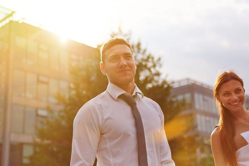 portrait of smiling man standing outdoors Adult Back Light Bonding Business Business People Businessman Businesswoman Career Couple Couple - Relationship Emotion Entrepreneur Face Focus On Foreground Formal Get Married Happiness Happy HEAD Joyful Lens Flare Lifestyles Love Man Men Merchant Nature Outdoors Outside Partnership People Portrait Real People Smile Smiling STAND Standing Summer Sun Sunlight Sunny Together Togetherness Trainee Two People Waist Up Wedding Woman Young Adult