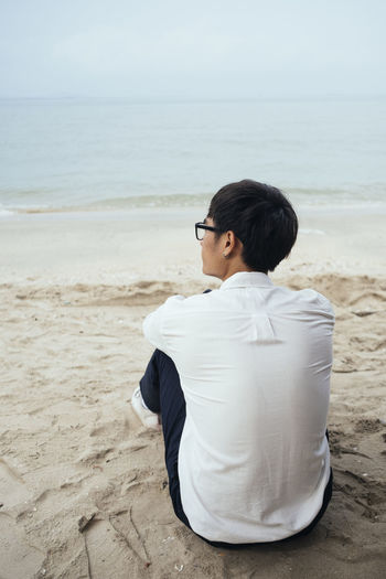 Man sitting on beach by sea against sky