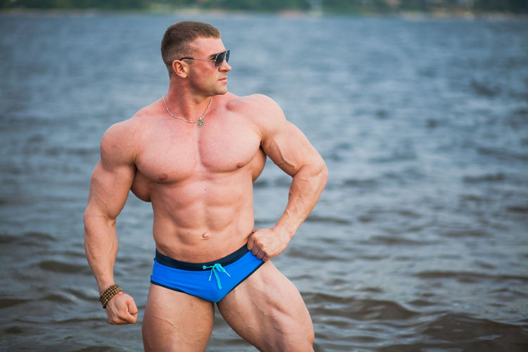 Shirtless bodybuilder while standing in sea
