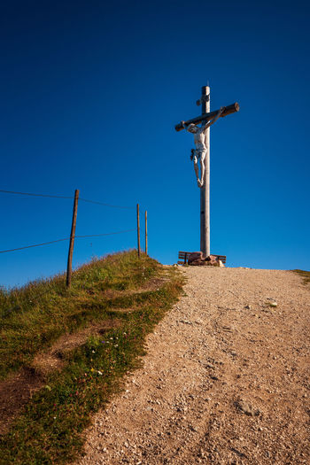 Low angle view of cross on field against clear blue sky