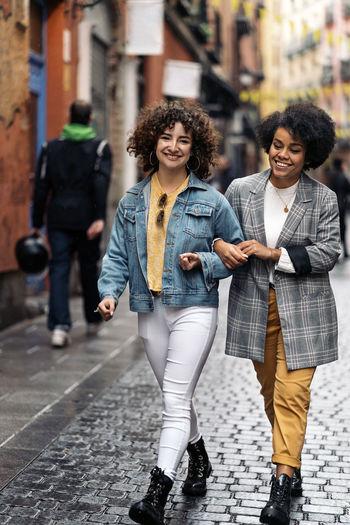 Happy friends walking on street in city