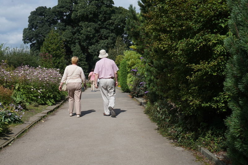 5329 Bonding Casual Clothing Couple - Relationship Day Day Out Flowers Footpath Green Color Growth Holiday Man Park - Man Made Space Path Pathway Person Plant Plants And Flowers Rear View Shadows Sky Togetherness Trees Woman Snap A Stranger