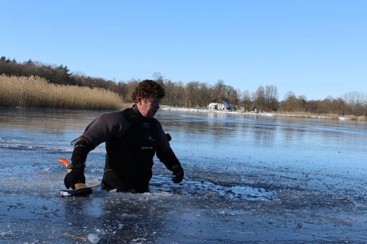 Full length of man in lake against sky during winter