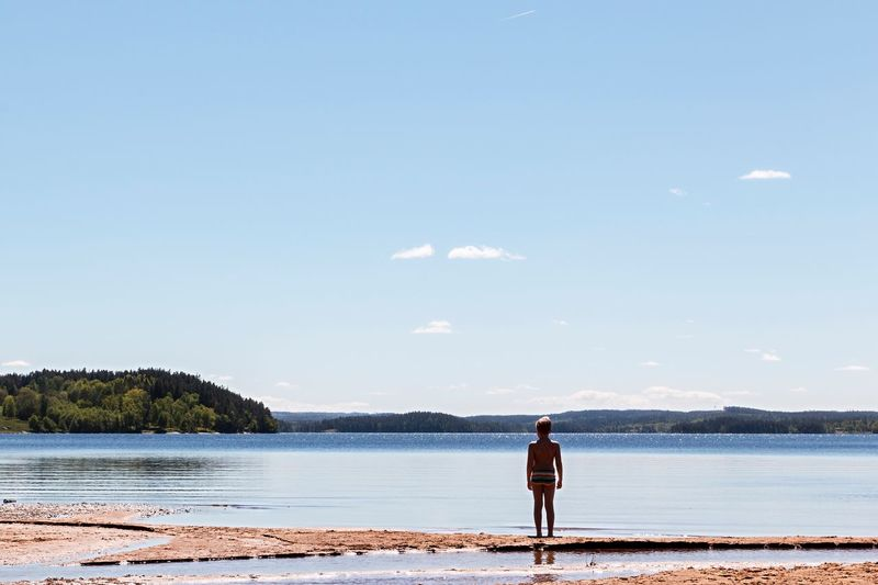 Shirtless Boy Standing On Sandbar By Sea Against Sky