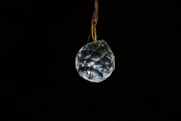 Close-up of crystal ball hanging against black background