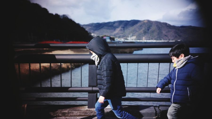 Side view of boys wearing warm clothing walking on bridge over river