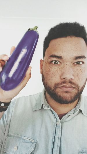 Portrait Of Serious Mid Adult Man Holding Eggplant