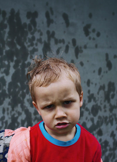 Little boy boy not happy with rain, funny face, wet child outdoors