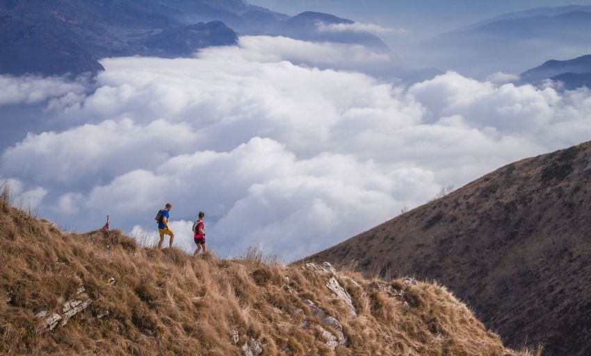 Side view of friends walking on mountain against cloudy sky