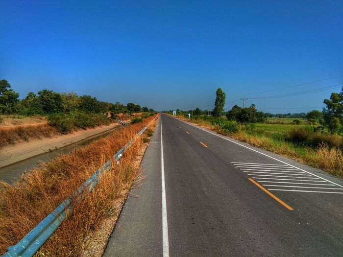 View of road against clear blue sky
