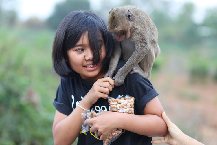 Close-up of girl feeding monkey