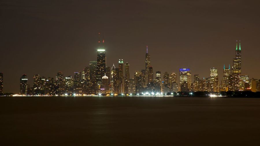 Sea By Illuminated City Skyline Against Sky At Night