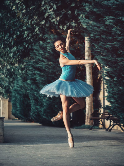 Ballet Dancer Dancing On Footpath Against Trees