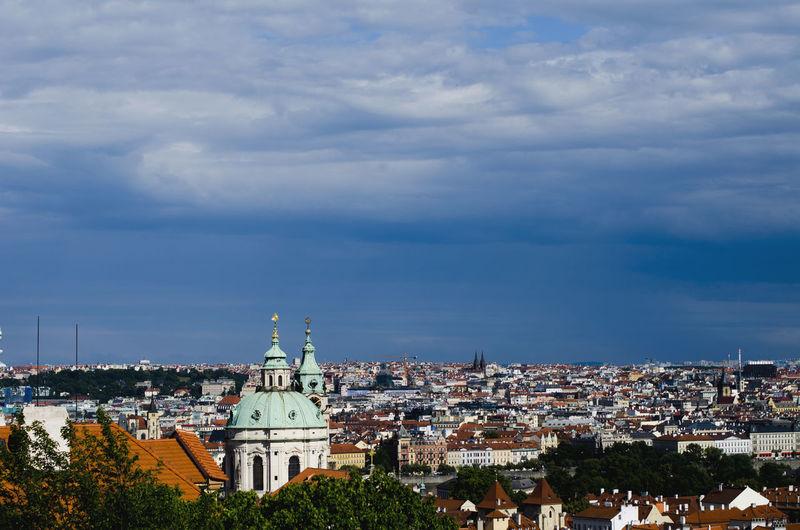View of cityscape seen through prague castle against cloudy sky