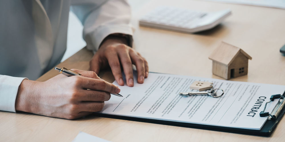 Close-up view hands of businesswoman signing leasing home documents and have a apartment keys on
