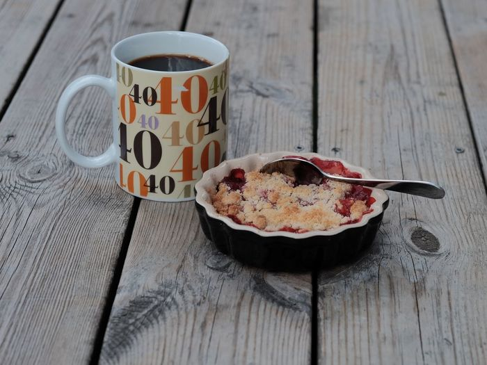 High Angle View Of Strawberry Tart With Coffee On Wooden Plank