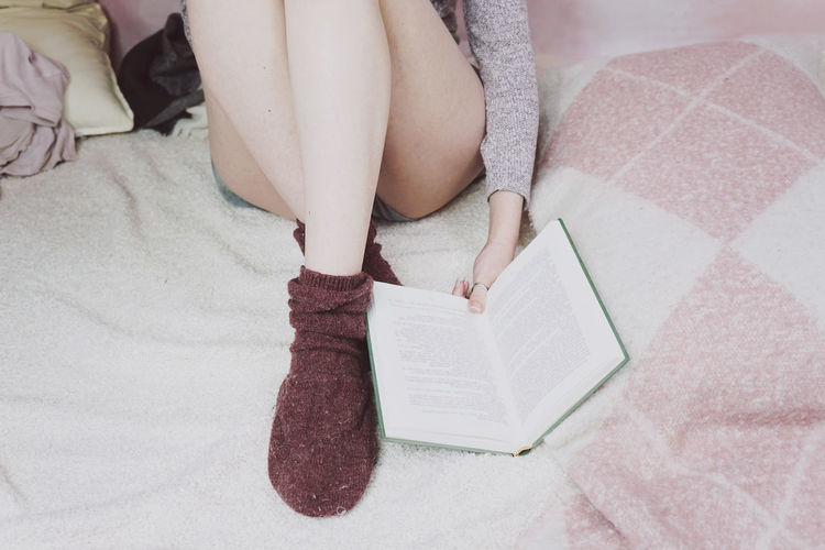 One Person Publication Indoors  Bed Real People Book Women Furniture Sitting Low Section High Angle View Reading Activity Relaxation Lifestyles Human Body Part Paper Body Part Human Leg Studying Femininity Young Adult Textured  Social Issues Legs