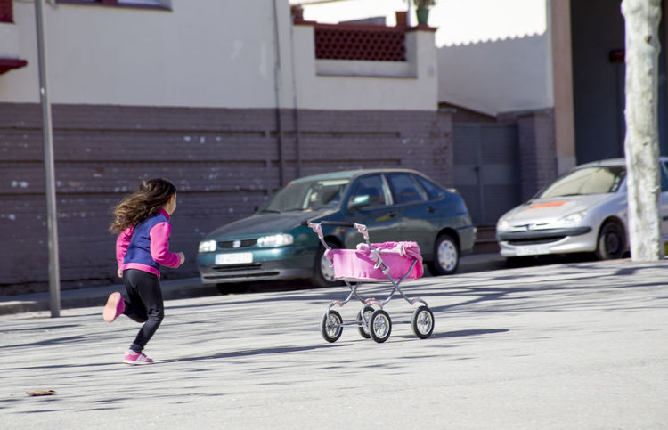 A little girl is running along the street, catching up with a tumbled toy carriage Catch Children Running Baby Carriage Carriage Child Childhood City City Life Girl Girl Running Mode Of Transportation Motion One Person Outdoors Pink Color Pram Street Toy Transportation