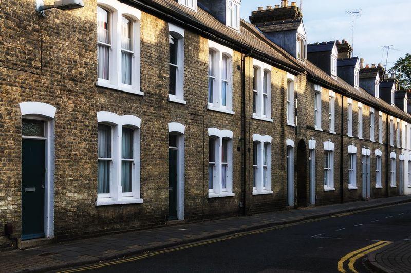 Road By Residential Buildings Against Sky