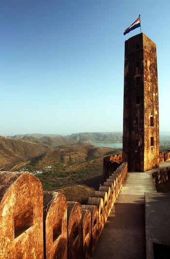 Indian flag on column at jaigarh fort against clear sky