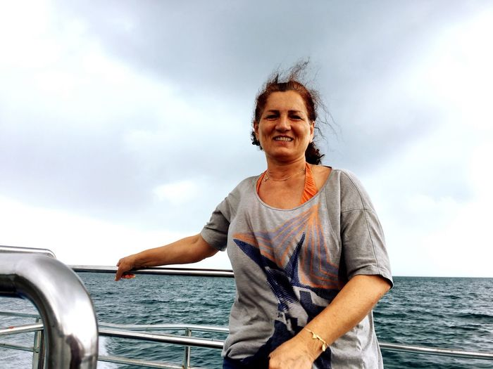 EyeEm Selects Sea Nautical Vessel Sky Cloud - Sky Water One Person Sailing Real People Mode Of Transport Mature Women Smiling Outdoors Happiness Transportation Day Mature Adult Leisure Activity Lifestyles Horizon Over Water Standing