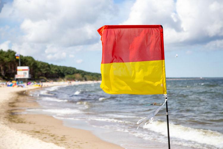Yellow flag on beach against sky
