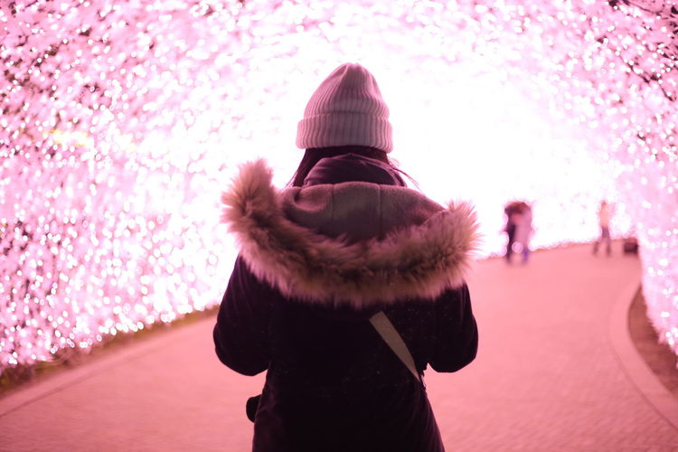 Rear view of woman standing against pink during winter