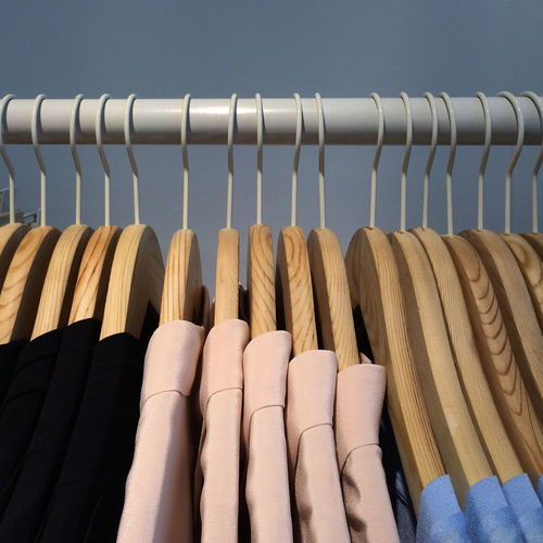Close-up of shirts on coathangers in row