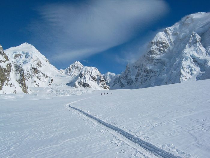 Diminishing perspective of ski tracks on glacier from mountaineering rope team with mountains