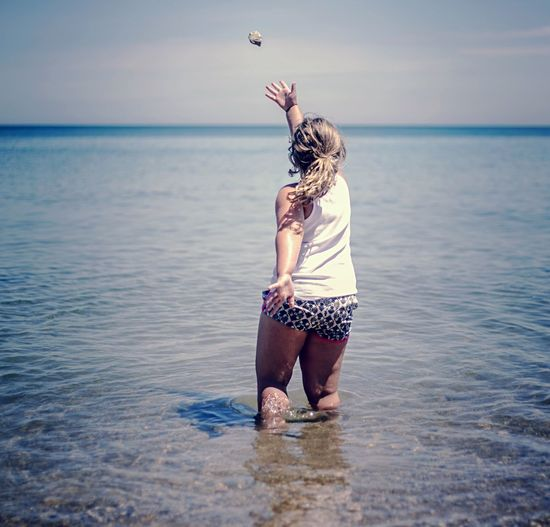 Rear View Of Girl Playing In Sea Against Sky