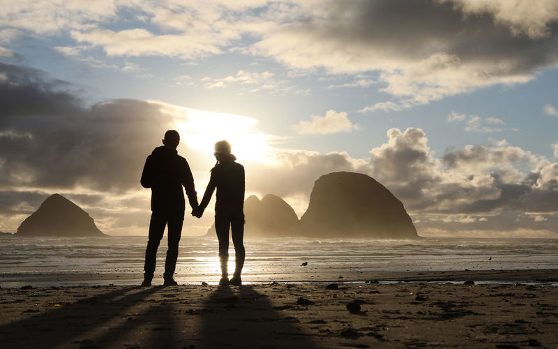 Couple standing on beach against sky during sunset