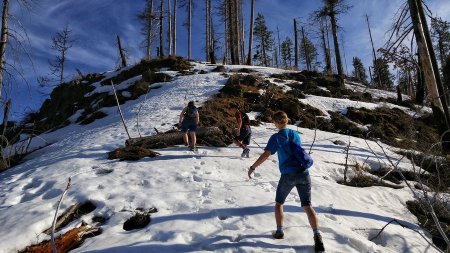 Low angle view of people hiking on snowcapped mountain during sunny day