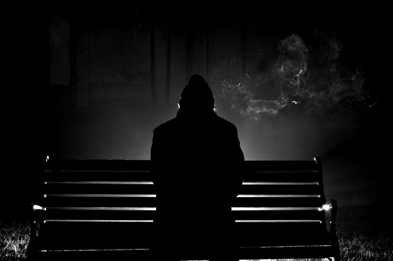 Rear view of silhouette man sitting on bench at night