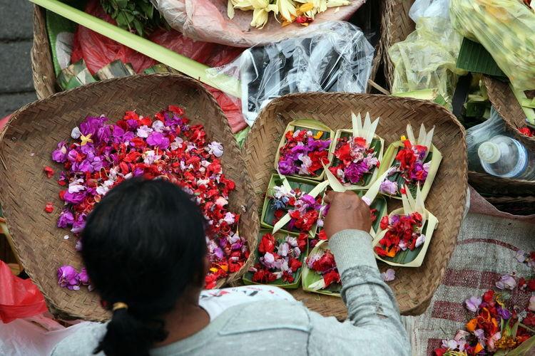 High Angle View Of Female Vendor Making Flower Garlands On Street Market