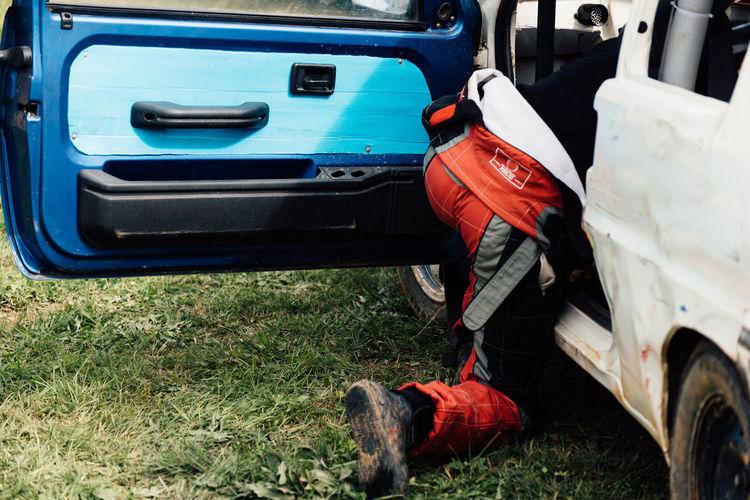 Man repairing car on field