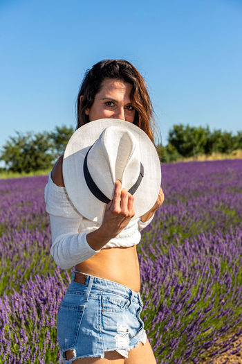 Half-length portrait of a young woman smiling behind a hat in a lavender field.